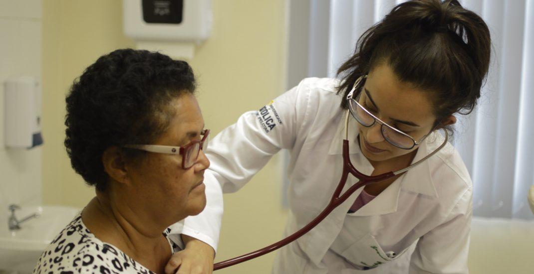 Acadêmica da medicina ausculta sistema circulatório de paciente.