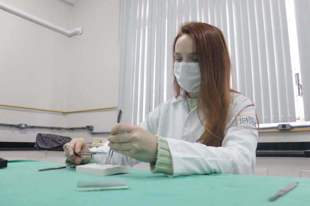 Aluna da Medicina de jaleco branco e máscara treina em um simulador sentada em uma mesa coberta por um tecido verde